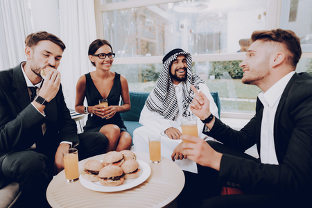 Arabian Businessman Is Having A Dinner With Partners. Money Investment. Talking With Managers. Partnership Agreement. Disdash And Keffiyeh Wearing. Eating A Burgers. Business Discussion.