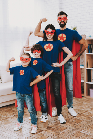 Young Family In Superhero Suits. Posing Concept. Masks And A Raincoats. Bright Room. Resting Together. Save The World. Get Ready. Strong And Powerful. Kids With A Parents. Active Lifestyle. Banco de Imagens