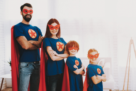 Young Family In Superhero Suits. Posing Concept. Masks And A Raincoats. Bright Room. Resting Together. Save The World. Get Ready. Arms Akimbo. Kids With A Parents. Active Lifestyle. Stock Photo