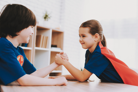 Strength Measuring. Kids In A Red And Blue Superhero Suits. Arm Wrestling Competition. Bright Room. Young Happy Family Holiday Concept. Resting Together. Healthy Lifestyle. Look At Each Other. Stock Photo