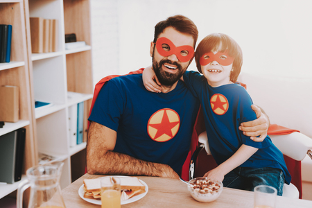 Young Family In Superhero Suits. Dinner Concept. Masks And Raincoats. Bright Room. Resting Together. Juice And Cereals. Get Ready. Healthy Lifestyle. Kids With A Parents. Active Leisure. Banco de Imagens - 107848622