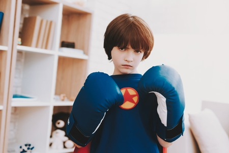 A Little Dark-haired Boy In A Superhero Shirt. Kid In A Boxing Gloves. Time For Action. Double Life. Alter Ego. Ger Ready. Strong And Powerful. Hidden Personality. Confidence And Bravery. Stock Photo