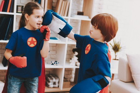 Children In Gloves Are Boxing In Superhero Suits. Time For Action. Double Life. Alter Ego. Healthy Lifestyle. Brother And Sister. Strong And Powerful. Kids Competition. Shot In The Head.