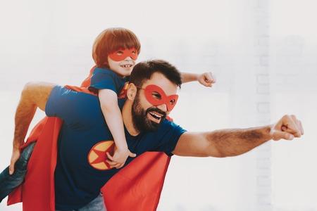 Vater und Sohn. Rote und blaue Superheldenanzüge. Masken und Regenmäntel. In einem hellen Raum posieren. Junge glückliche Familienferienkonzept. Zusammen ruhen. Rette die Welt. Bereit machen. Stark und kraftvoll. Standard-Bild