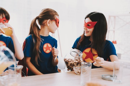 Young Family In Superhero Suits. Dinner Concept. Masks And Raincoats. Bright Room. Resting Together. Juice And Cereals. Get Ready. Healthy Lifestyle. Kids With A Parents. Active Leisure. Banco de Imagens