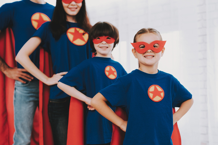 Young Family In Superhero Suits. Posing Concept. Masks And A Raincoats. Bright Room. Resting Together. Save The World. Get Ready. Arms Akimbo. Kids With A Parents. Active Lifestyle. Banco de Imagens