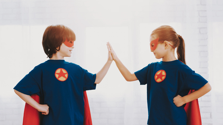 Children In A Superhero Suits. Posing Concept. Masks And A Raincoats. Bright Room. Resting Together. Save The World. Get Ready. High Five. Happy Childhood. Brother And Sister. Young Leaders.