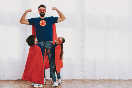 Young Family In Superhero Suits. Posing Concept. Masks And Raincoats. Bright Room. Resting Together. Save The World. Get Ready. Hand In Hand. Kids With A Parents. Active Lifestyle.