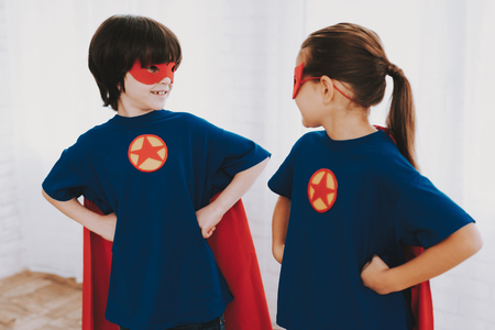 Children In A Superhero Suits. Posing Concept. Masks And A Raincoats. Bright Room. Resting Together. Save The World. Get Ready. Arms Akimbo. Happy Childhood. Brother And Sister. Young Leaders.