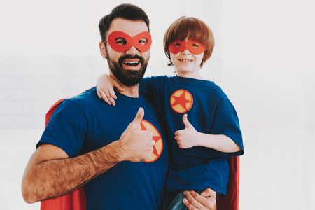 Father And Son. Red And Blue Superhero Suits. Masks And Raincoats. Posing In A Bright Room. Young Happy Family Holiday Concept. Resting Together. Save The World. Get Ready. Thumbs Up.