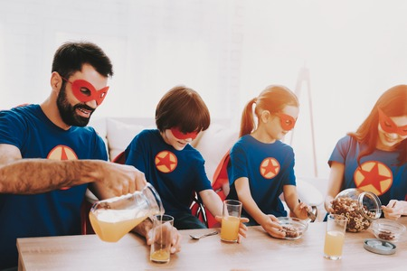 Young Family In Superhero Suits. Dinner Concept. Masks And Raincoats. Bright Room. Resting Together. Juice And Cereals. Get Ready. Healthy Lifestyle. Kids With A Parents. Active Leisure. 版權商用圖片