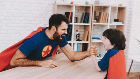 Father And Son. Red And Blue Superhero Suits. Arm Wresling Competition. Bright Room. Young Happy Family Holiday Concept. Resting Together. Healthy Lifestyle. Active Leisure. Holiday Joy.