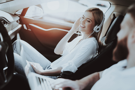 Man Works With Laptop. Girl In Headphones. Tesla Car. Front Seat. Innovation Technology. New Generation Electro Hybrid Vehicle. Luxury Design. Futuristic Power. Resring Together. Test Driving.
