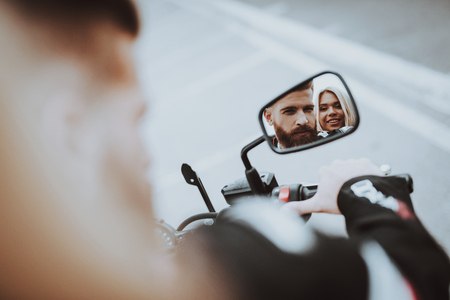 Man And Women Stare In A Bike Rearview Mirror. Bikers Concept. Going For Ride. Fashion Riders. Confident Staring. Speed Vehicle. Biker With A Beard. Motorbike Concept. Tripping Together. 版權商用圖片