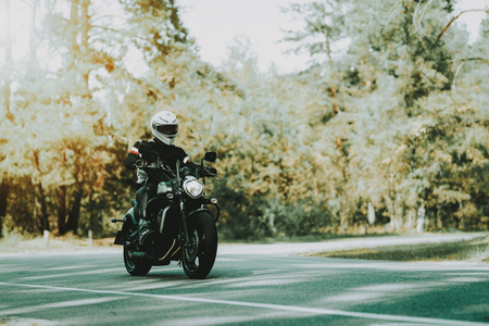 Biker In Helmet Is Riding On Highway In A Forest. Speed Vehicle. Cool rider With A Leather Jacket. Motorbike Concept. Classic Style. Ready To Drive. Speed Motorcycle In A Forest. Hidden Face. Stock Photo