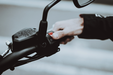 Hand Of A Biker Laying On Motorcycle Steering. Going For Ride. Speed Vehicle. Motorbike Concept. Tripping Together. Speed Choosing. Journey Start. Ready To Go. Power Button. Black Jacket. Stock Photo