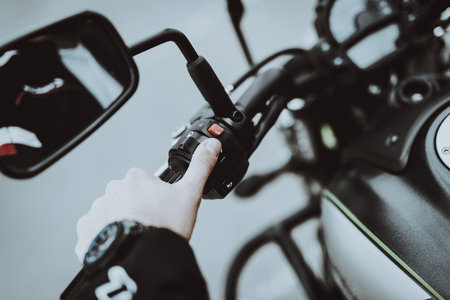 Hand Of A Biker Laying On Motorcycle Steering. Going For Ride. Speed Vehicle. Motorbike Concept. Tripping Together. Speed Choosing. Journey Start. Ready To Go. Power Button. Black Jacket. Stock Photo - 107994106