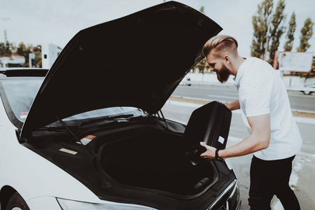 Man Is Putting A Bag In Tank Of Tesla Car. Charge Station. Automobile Concept. Innovation Technology. New Generation Electro Hybrid Vehicle Plugin. Ecology Protection. Futuristic Power.
