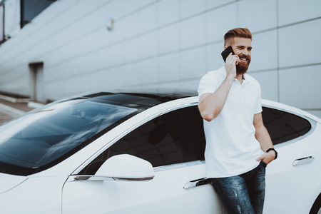 Man Talks On Phone Near Tesla Car. Charge Station. Automobile Parking Lot. Innovation Technology. New Generation Electro Hybrid Vehicle. Ecology Station. Futuristic Power. Gadget Concept. Stock Photo - 107974058