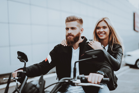 Man And Women Are Sitting On Motorcycle. Going For Ride. Fashion Riders. Confident Staring. Speed Vehicle. Biker With A Beard. Motorbike Concept. Classic Style. Ready To Drive. Tripping Together.
