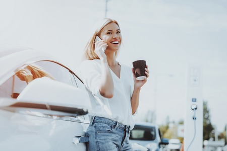 Car Charge Concept. Girl Talks The Phone. Automobile Station. Innovation Technology. New Generation Electro Hybrid Vehicle Plugin. Ecology Station. Futuristic Power. Cup Of Coffee. Stock Photo - 108171003