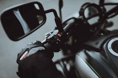 Hand Of A Biker Laying On Motorcycle Steering. Going For Ride. Speed Vehicle. Motorbike Concept. Tripping Together. Speed Choosing. Journey Start. Ready To Go. Power Button. Black Jacket. Stockfoto