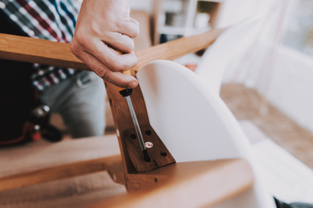 Young Man Assembling Coffee Table and Stools. Furniture Fittings. Engineer with Tool. Young Man at Home. Wooden Coffee Table. Selfmade Furniture. Man and Hobby. White Table in Room. Фото со стока
