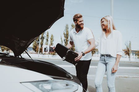 Man And Woman Putting A Bag In Tank Of  Car. Charge Station. Automobile Testing. Innovation Technology. New Generation Electro Hybrid Vehicle Plugin. Sunny Day. Futuristic Power. Stock Photo - 108171564