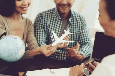Hombre y mujer joven en agencia de viajes con gerente. Consultor en Agencia de Viajes. Concepto de viaje familiar. Avión de juguete en las manos. Vacaciones de fin de semana. Conceptos turísticos. Pareja de viaje.