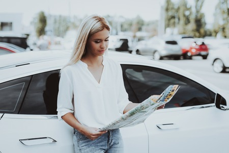 Girl Is Looking On Map Standing Next To Tesla Car. Charge Station. Automobile Background. Journey Planning. New Generation Electro Hybrid Vehicle. Sunny Day. Find A Way. Parking Lot. Stock Photo - 107974070