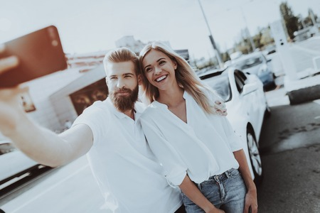 Couple Is Making A Selfie With   Car Behind. Happy Together. Photo With A Car. New Generation Automobile. Electro Hybrid Vehicle. Innovation Technology. Parking Lot. Charge Station. Stock Photo - 108172249