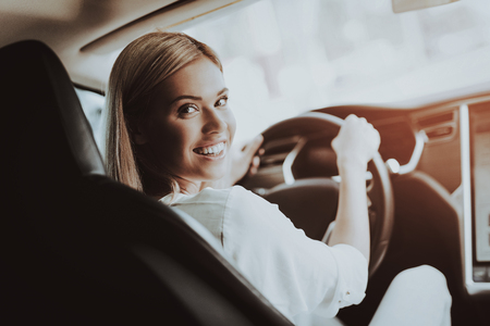 Woman In Tesla Car. Behind The Wheel Concept. Innovation Technology. New Generation Electro Hybrid Vehicle. Luxury Design. Futuristic Power. Hand On Display. Inside View. Front Seat.