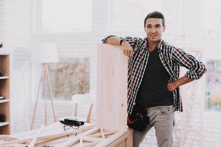 Young Man Assembling Wooden Bookshelf at Home. Wooden Bookcase. Selfmade Furniture. Man and Hobby. White Room. Engineer with Tool. Young Man at Home. Homemade Decoration. Modern Furniture.