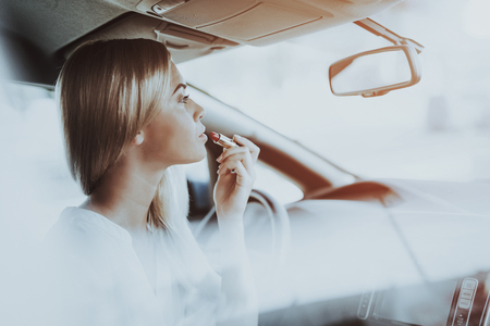 Woman Is Doing Makeup In Front Seat Of Tesla Car. Innovation Technology. New Generation Electro Hybrid Vehicle. Luxury Design. Futuristic Power. Hand On Display. Inside View. Front Seat.