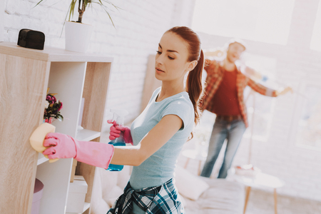 Young Couple in Checkered Shirts Cleaning Room. Sanitary at Home. Hands in Rubber Gloves. Housekeeping Concept. Cleaning with Sponge. Using Spray. Family at Home. Couple Indoor. Sanitary Concept.