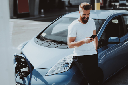 Tesla Car Charge Concept. Man With Talking On Phone Background. Automobile Station. Innovation Technology. New Generation Electro Hybrid Vehicle Plugin. Ecology Station. Futuristic Power. Stock Photo - 108178175