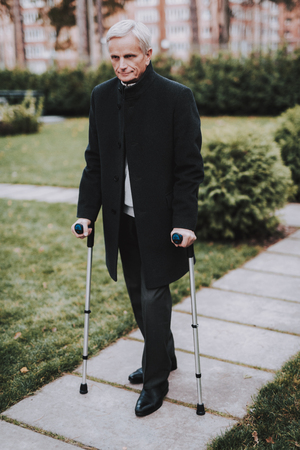 Old Man in Suit Walks with Walkers for Adults. Healthcare Concept. Disabled Pensioner. Walking in Park. Green Grass. Man in Black Suit. Recovery and Therapy Concepts. Grandfather in Park.