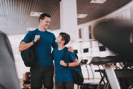 Young Father and Son near Treadmills in Modern Gym. Healthy Lifestyle Concept. Sport and Training Concepts. Modern Sport Club. Sport Equipment. Family Sport. Running Tracks. Parent with Child. Stock Photo