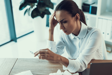 Young Sick Woman in White Shirt Sitting in Office.Healthcare Concept. Modern Office. Sick Worker. Healthcare in Office. Wooden Table. Digital Device. Laptop on Desk. Young Woman in Office. Reklamní fotografie