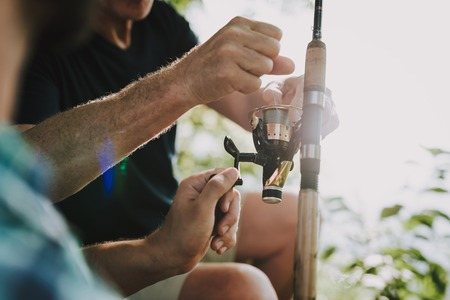 Old Father with Bearded Son Fishing on River in Summer. Relaxing Outdoor. Bearded Young Man. Men near Lake. Fishing Rod in Hands. Sports in Summer. Weekend on River. Adult Fishermen.