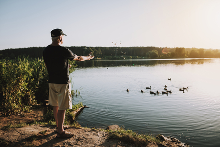 Old Man in Cap Feeding Ducks on River in Summer. Animals on Lake. Relaxing Outdoor. Man near Lake. Old Man in Cap. Weekend on River. Bread Crumbs in Hands. Wild Birds. Sunset on Lake. Stock Photo - 108118085