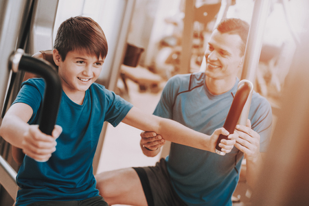 Young Father and Son Doing Exercises in Sport Club. Healthy Lifestyle Concept. Sport and Training Concepts. Modern Sport Club. Sport Equipment. Family Sport. Training Apparatus. Parent with Child. Stock Photo