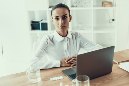 Young Sick Woman in White Shirt Sitting in Office.Healthcare Concept. Modern Office. Sick Worker. Healthcare in Office. Wooden Table. Digital Device. Laptop on Desk. Young Woman in Office.