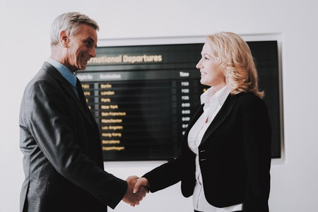 Businesswoman Saying Goodbye to Businessman in Airport. Business Tour. People with Baggage. Travelers on Vacation. Business Travels Concept. Senior Person in Airport. Old Couple in Voyage.