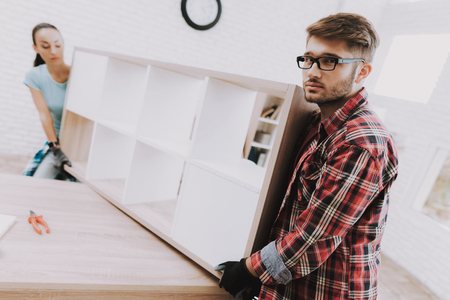 Young Couple Assembling Wooden Bookshelf at Home. Wooden Bookcase. Selfmade Furniture. Family at Home. White Room. Engineer with Tool. Homemade Decoration. Modern Furniture. Woman with Tools.