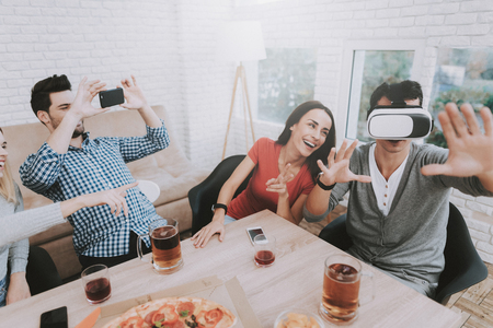 Young Smiling People Have Fun with Virtual Reality Device on Party at Home. Indoor Fun. Young Smiling Girl. Young Smiling Guy. Sitting at Table. Party with Friends. Indoor Activities Concept. Stok Fotoğraf