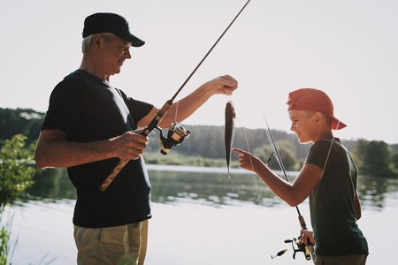Happy Grandfather and Grandson Fishing on River in Summer. Relaxing Outdoor. Old Man and Boy. Men near Lake. Fishing Rod in Hands. Sports in Summer. Weekend on River. Aged Fisherman.