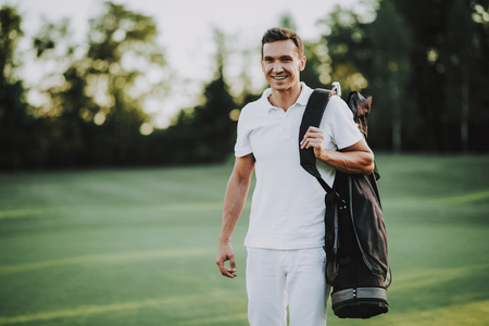 Young Man in White Clothes Playing Golf on Field. Relaxing in Golf Club. Sports in Summer. Outdoor Fun in Summer. Happy Young Man. Healthy Lifestyle Concept. Man it White Shirt. Green Grass.