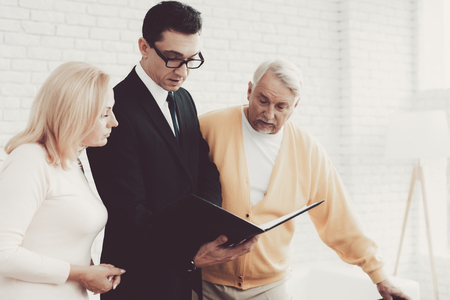 Old Man and Woman Visiting Young Lawyer in Office. Important Documents. Modern Law Office. Grandfather and Grandmother. People with Gray Hair. Young Advocate. Justice and Law Concepts. Stock Photo