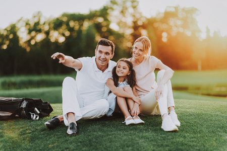 Happy Young Family Sitting on Golf Field in Summer. Relaxing in Golf Club. Sports in Summer. Outdoor Fun in Summer. Family Fun. Healthy Lifestyle Concept. Little Girl. Green Grass.